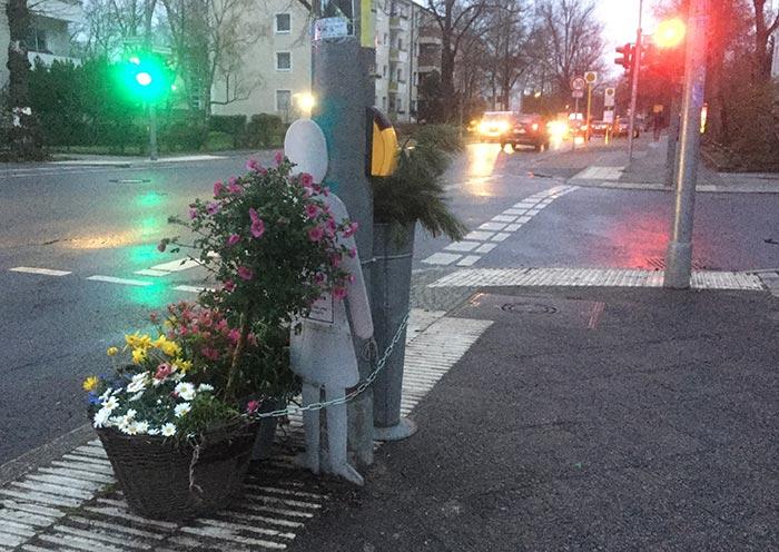 Erinnerungsort an eine getötete Fußgängerin: Blumen und weiße Silhouetten-Figur an einer Ampel