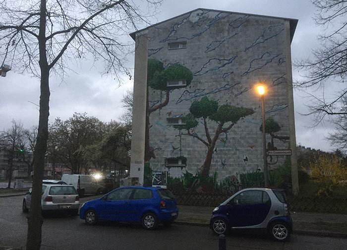 Wandgemälde mit Bäumen und Wolken, davor eine erleuchtete Straßenlaterne