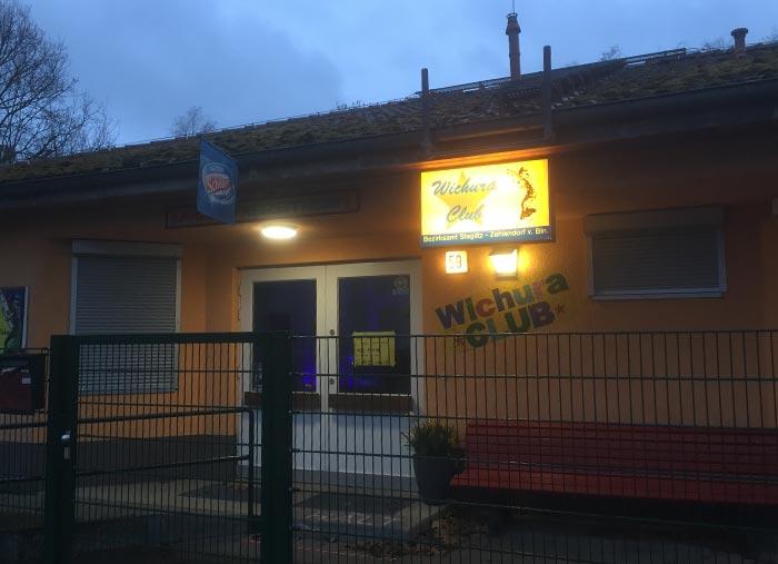 Gebäude Wichura Club im Halbdunkel mit erleuchtetem Schild