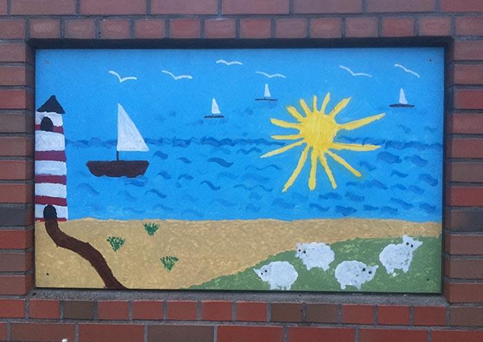 Kinderbild mit Meer, Strand, Leuchtturm und Sonne an einer Backstein-Mauer