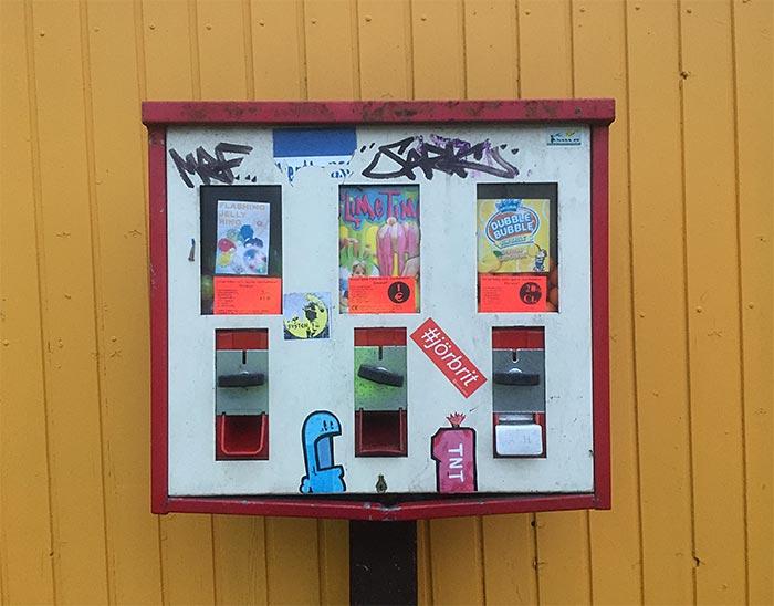 Roter Kaugummi-Automat vor einer gelben Holzwand