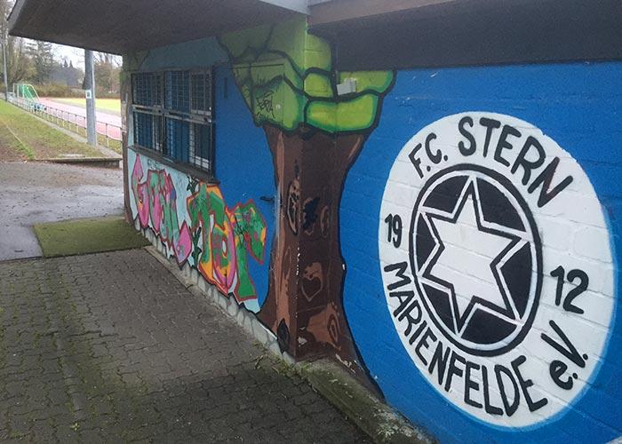 Kassengebäude an einem Fußballplatz, blau bemalt mit weiß-schwarzem Logo F.C. Stern Marienfelde