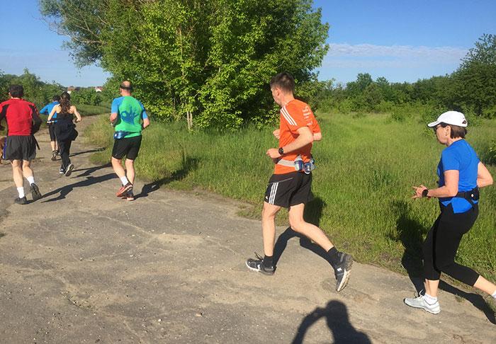 Läufer*innen auf einem brüchig asphaltierten Weg im Grünen