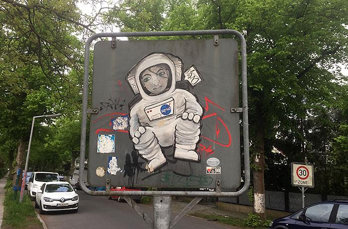 Graffiti einer hockenden Astronautin auf der Rückseite eines Verkehrsschilds