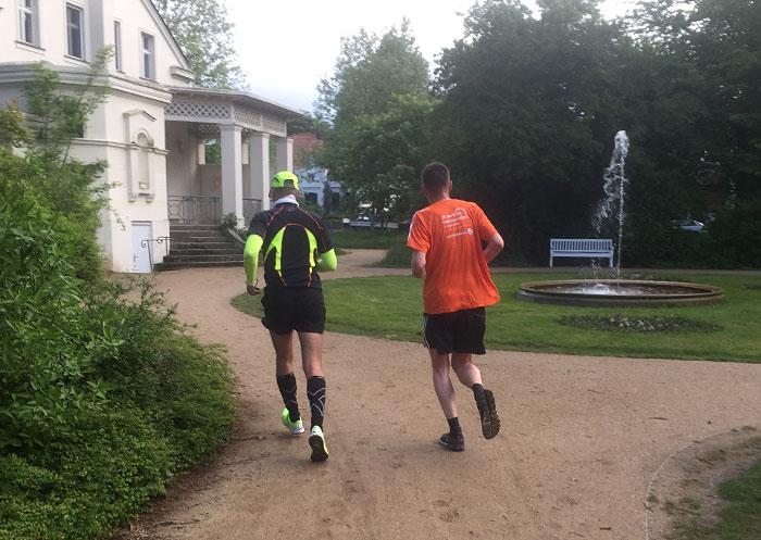 Zwei Läufer am Gutshaus Marienfelde mit Springbrunnen