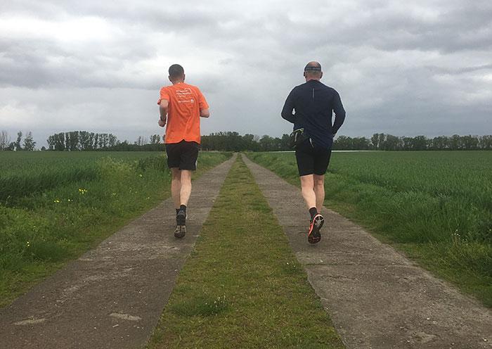 Läufer auf Betonplattenweg zwischen Feldern