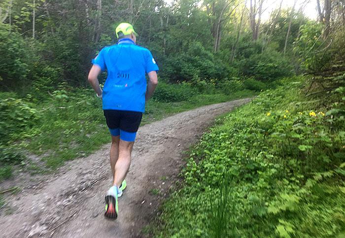 Läufer läuft einen Hügelpfad hinauf