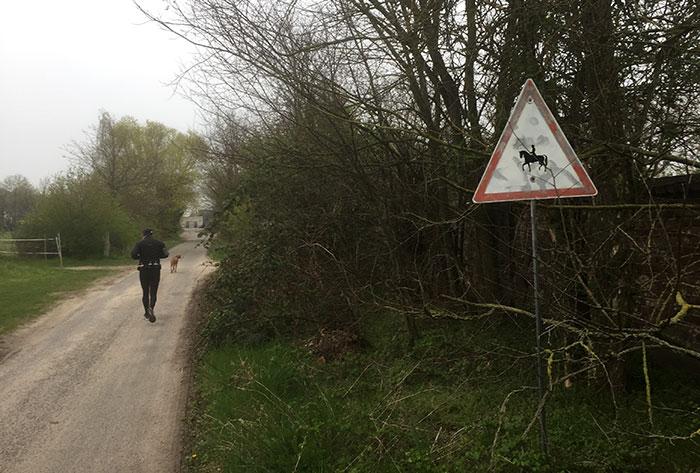 Läufer auf Weg, an der Seite Reiter-Schild