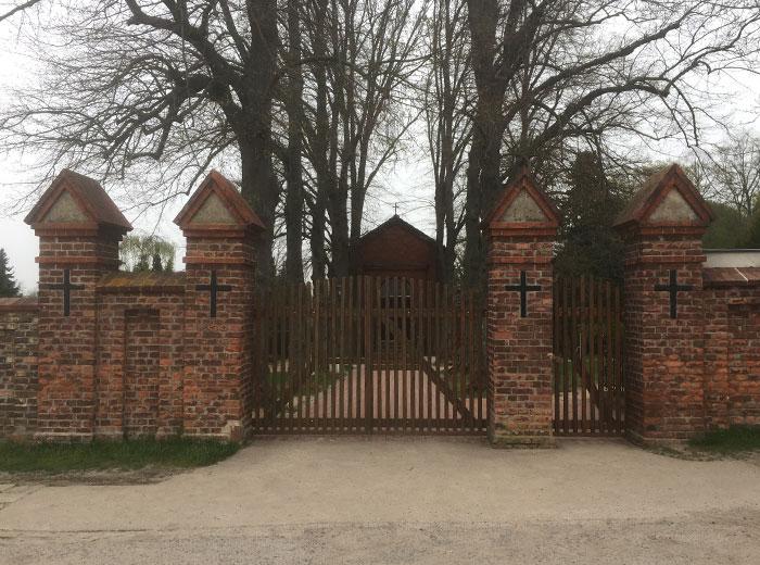 Eingang zum Friedhof Mahlow mit roter Backsteinmauer und Kreuzen