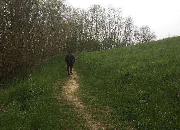 Läufer auf Pfad an einer hügeligen Wiese