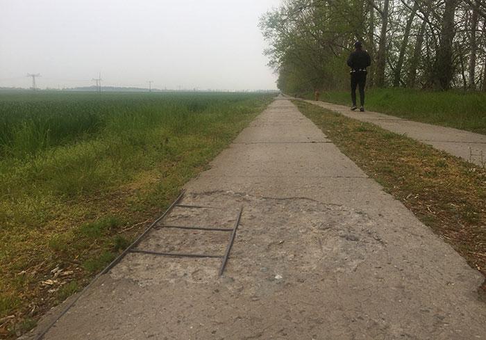 Plattenweg bis zum Horizont, an dem links eine waldige Erhebung zu sehen ist