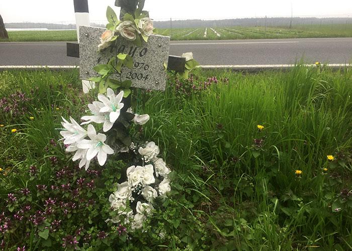 Gedenkkreuz mit weißen Blumen für einen Verkehrstoten an der Birkholzer Straße