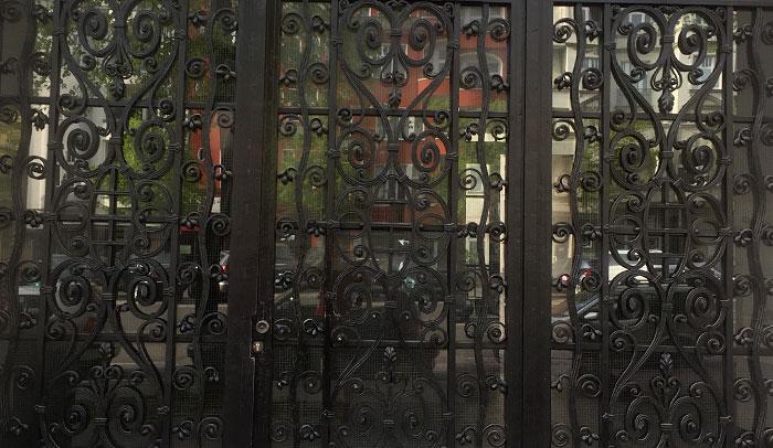 Kunstvoll verschlungenes dunkles schmiedeeisernes Gitter vor Hauseingang