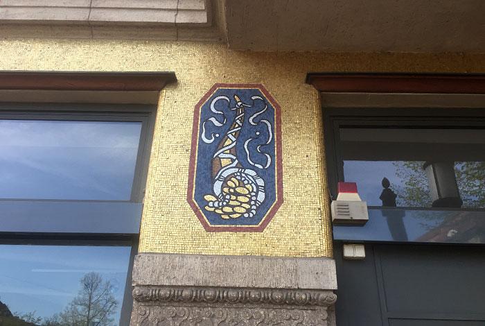 Goldene Mosaik-Plättchen an einem Gebäude, darin Motiv mit Füllhorn und Münzen