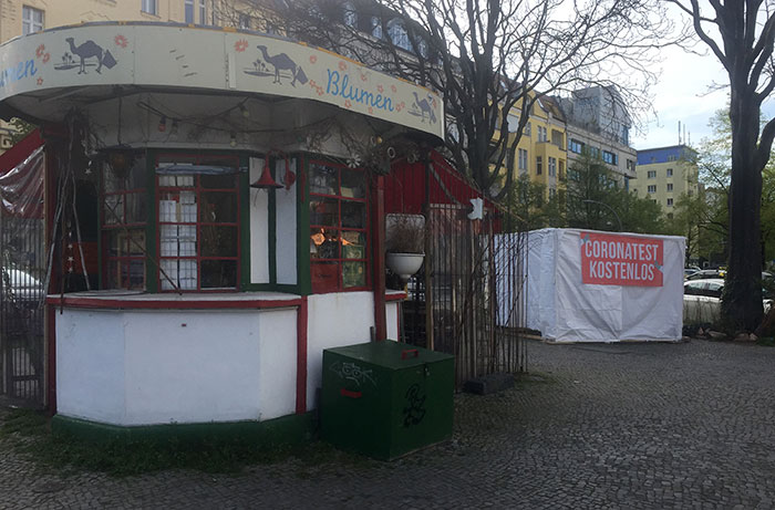 "Blumen-Kiosk, daneben Schild ""Coronatest kostenlos"""