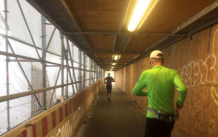 Läufer in einer gelb beleuchteten Baustellen-Unterführung