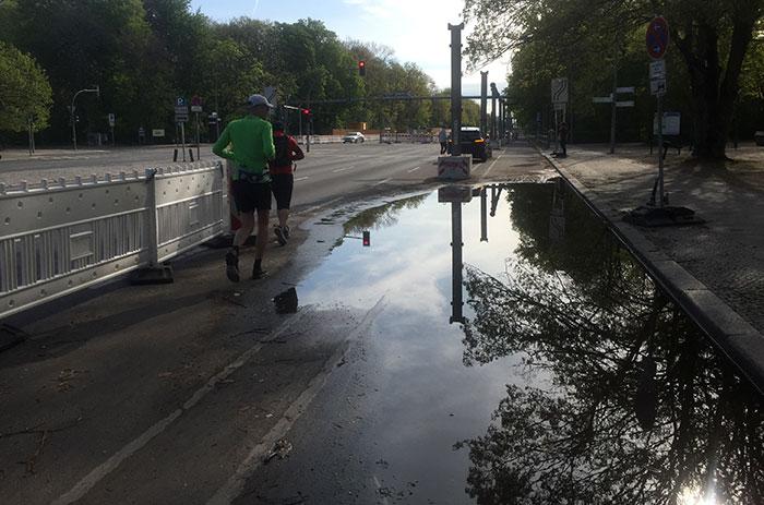 Läufer neben einer großen Pfütze auf der Straße des 17. Juni