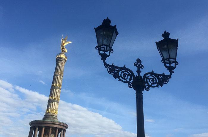 Golden glänzende Siegessäule und dunkle historische Straßenlaterne