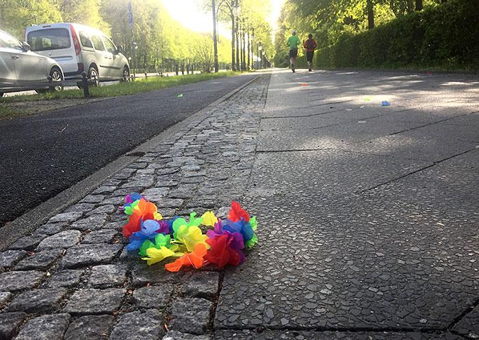 Bunte Plastikblumen-Kette auf Fußweg, im Hintergrund Läufer