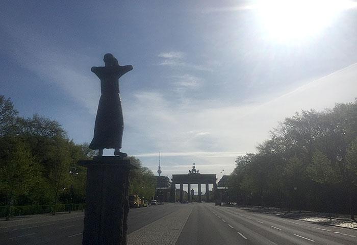 Statue Der Rufer, im Hintergrund der Fernsehturm und das Brandenburger Tor im Gegenlicht