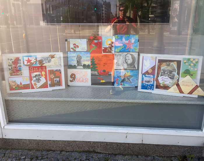 Zeichnungen und Illustrationen mit russischer Schrift zum 9. Mai im Fenster des ehemaligen Aeroflot-Gebäudes