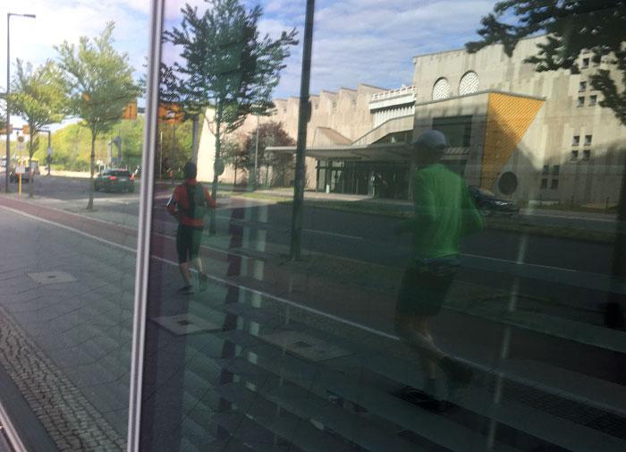 Spiegelung Läufer und Musikinstrumentenmuseum in einer Glasfassade