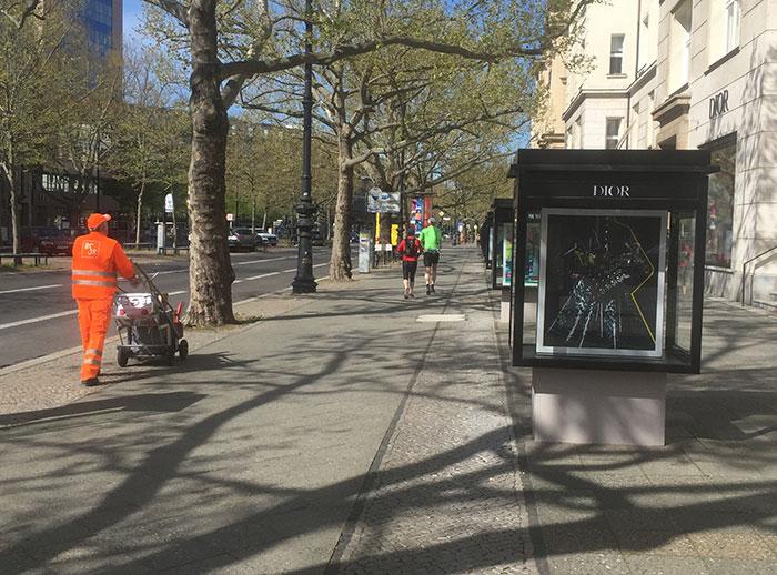 BSR-Stadtreiniger in oranger Arbeitskleidung und Schaukasten von Dior