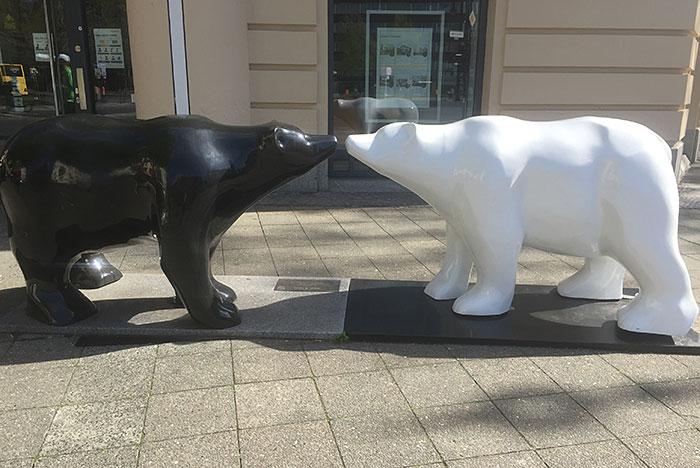 Skulptur: Ein schwarzer und ein weißer Bär stehen Schnauze an Schnauze
