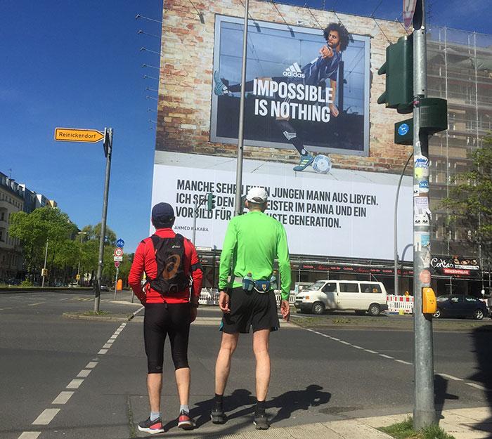 """Läufer vor riesengroßer Bannerwerbung """"Impossible is nothing"""" an einem Gebäude"""