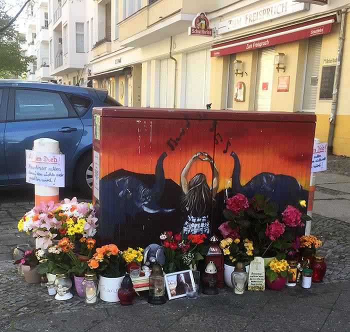 Private Gedenkstelle mit vielen Blumen an einem bemalten Trafokasten