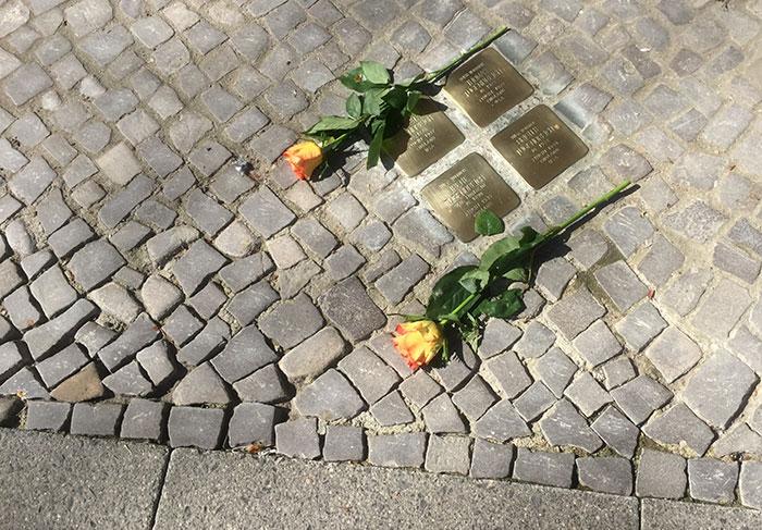 Zwei gelbrote Rosen auf dem Gehweg bei vier goldenen Stolpersteinen (Gedenktafeln)