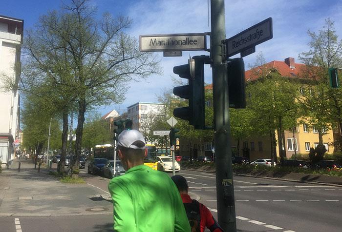 Läufer unter dem Straßenschild Marathonallee