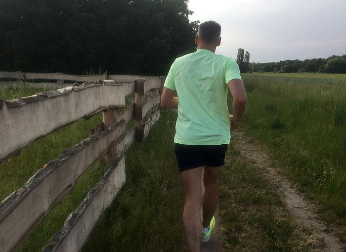 Läufer am Feldrand neben Holzzaun