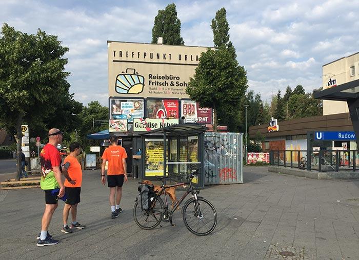 Läufer machen Pause am U-Bahnhof Rudow, in der Bildmitte steht ein Fahrrad.
