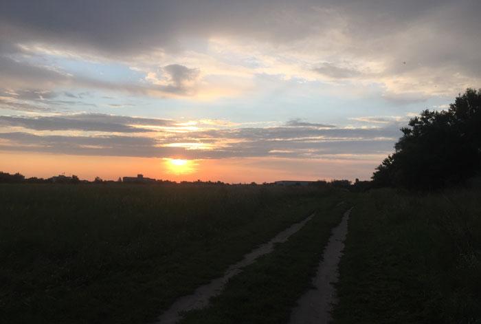 Feldweg im Dunkeln, im Hintergrund ein schöner Sonnenaufgang
