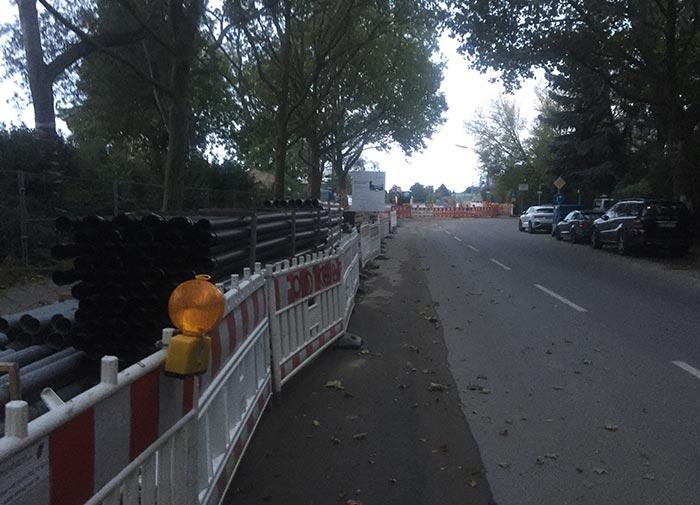 Blick entlang der Säntisstraße auf die Baustelle am Bahnübergang, links Sperrzäune, dahinter gelagerte Rohre