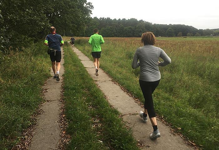 Läuferin und Läufer auf Plattenweg am Feldrand