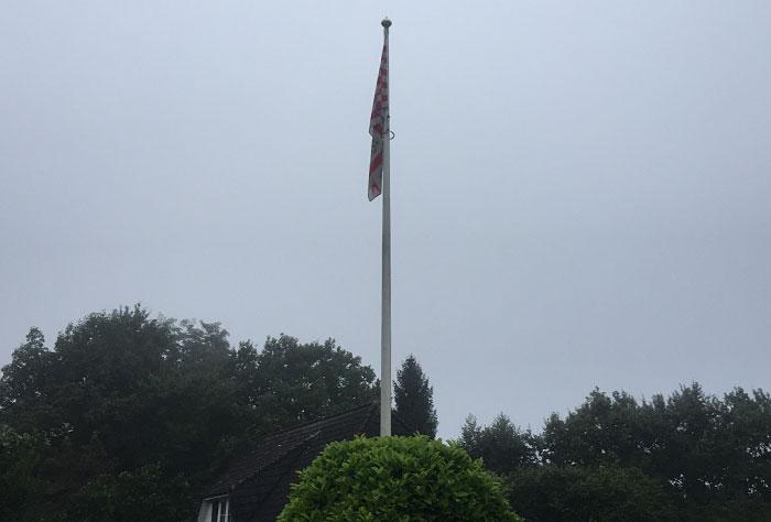 Schlapp herunterhängende Bremer Flagge vor einem grauen Himmel