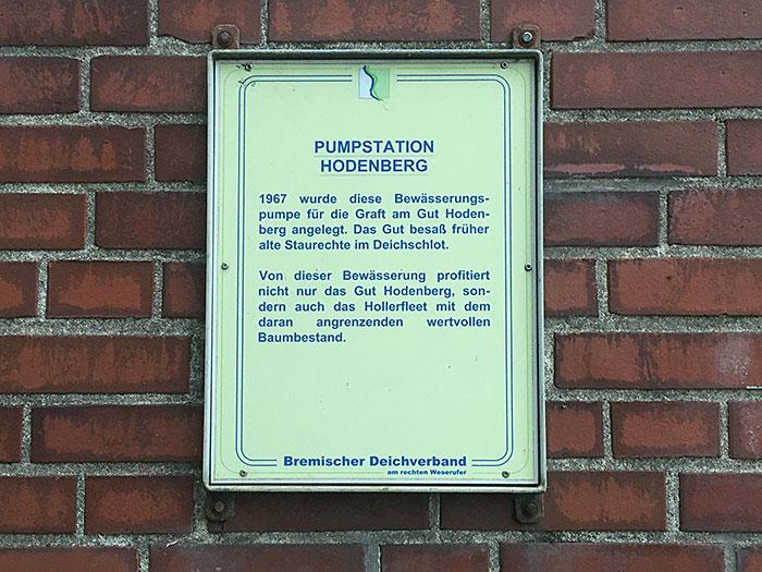 Schild mit Informationen zur Pumpstation Hodenberg auf Ziegelwand