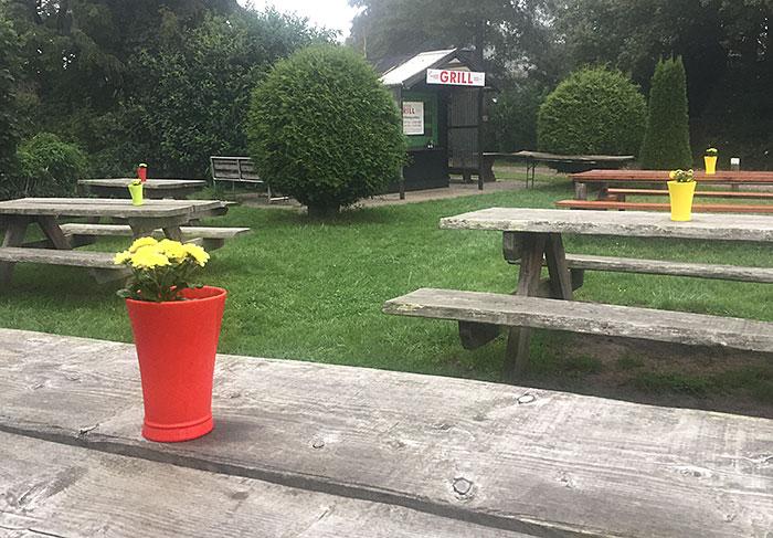 """Blumen in roter Vase auf einem Holztisch, im Hintergrund Hütte """"Grill"""""""
