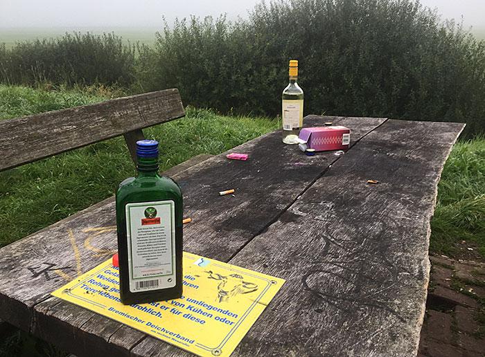 Holztisch eines Rastplatzes mit leeren Alkohol-Flaschen