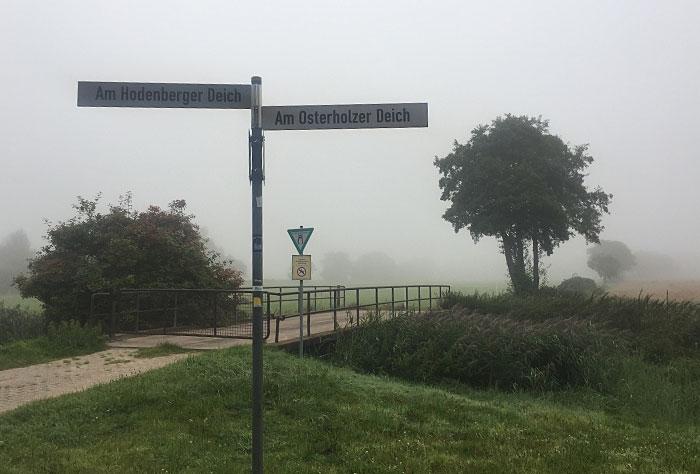 Schild: links Am Hodenberger Deich, rechts Am Osterholzer Deich