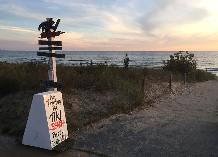 Schild am Strand mit hinweis auf Tiki Beach Party