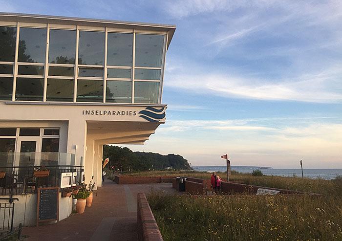 """Verglastes Gebäude, das über die Promenade ragt, beschriftet mit """"Inselparadies"""""""