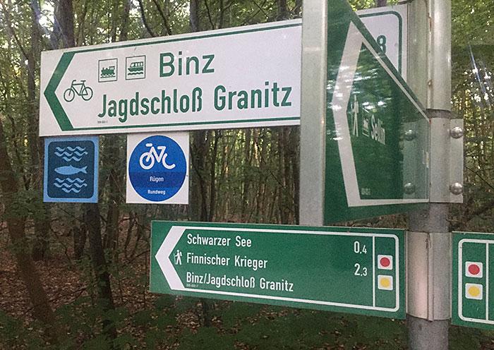 Schilder mit Richtung Binz, Schloss Granitz, Schwarzer See, Finnischer Krieger und Sellin