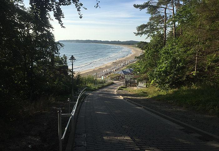 Blick die gepflasterte Straße hinunter auf die Gastronomie, die Strandkörbe und das Meer