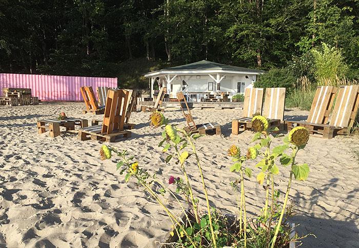 Weißer Pavillon, davor auf Strandsand aus Holzpaletten gebaute Sitzmöbel