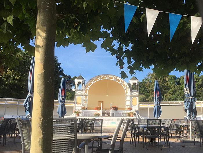 Bühne der Kurmuschel Göhren, Stühle, eingeklappte Sonnenschirm, oben blau-weiße Wimpele