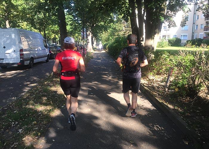Läuferin und Läufer auf dem baumbestandenen Fußweg