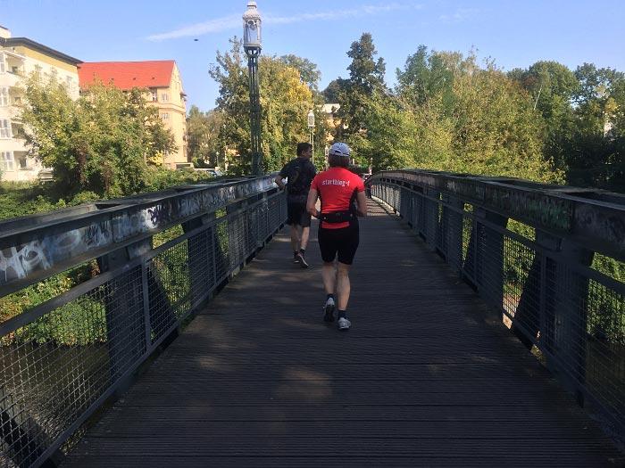 Läuferin und Läufer auf einer schmalen Brücke über den Teltowkanal